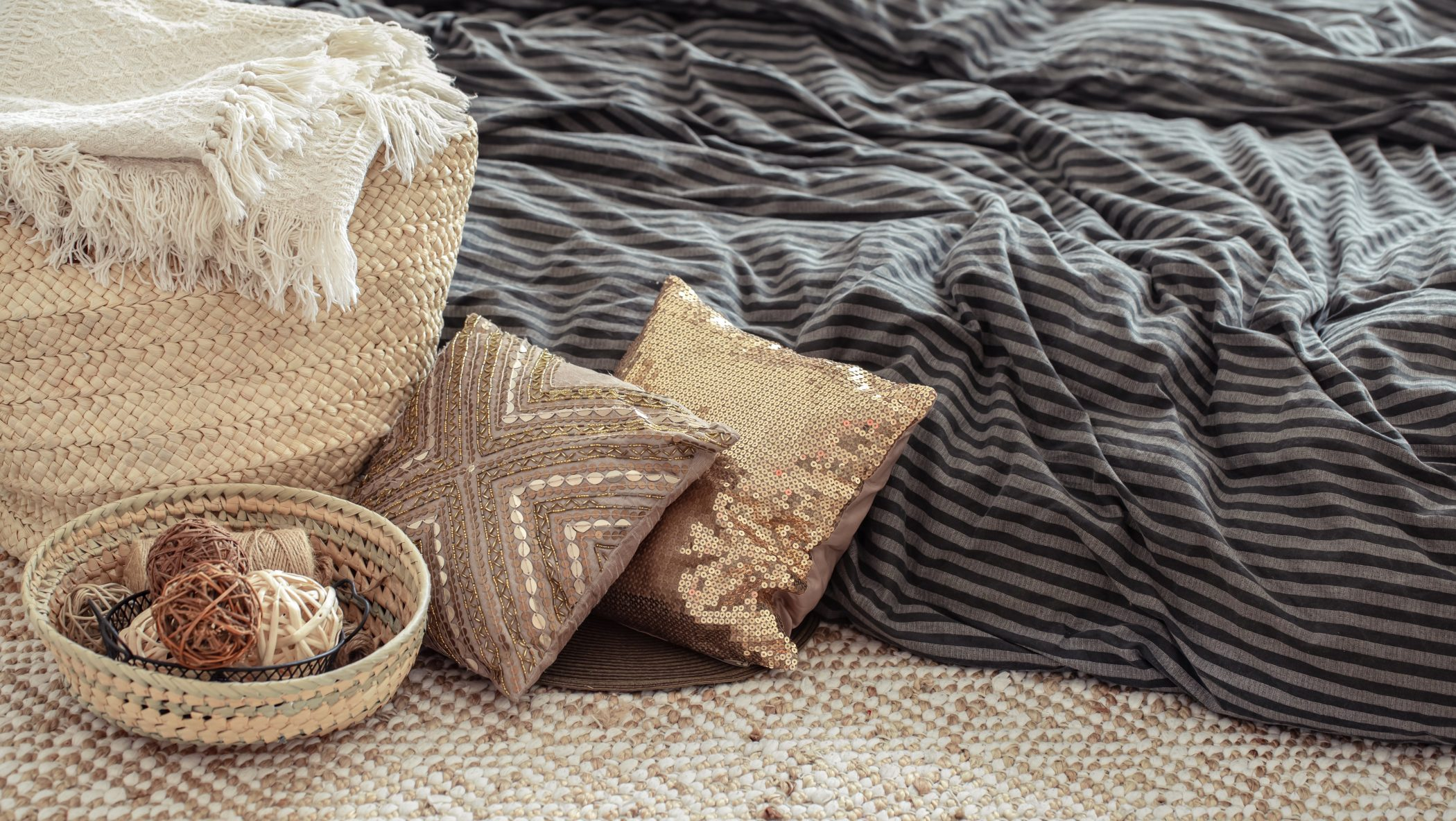 Decorative items in a cozy home interior. Wicker straw large bag, and decorative elements. Concepts of style and comfort.